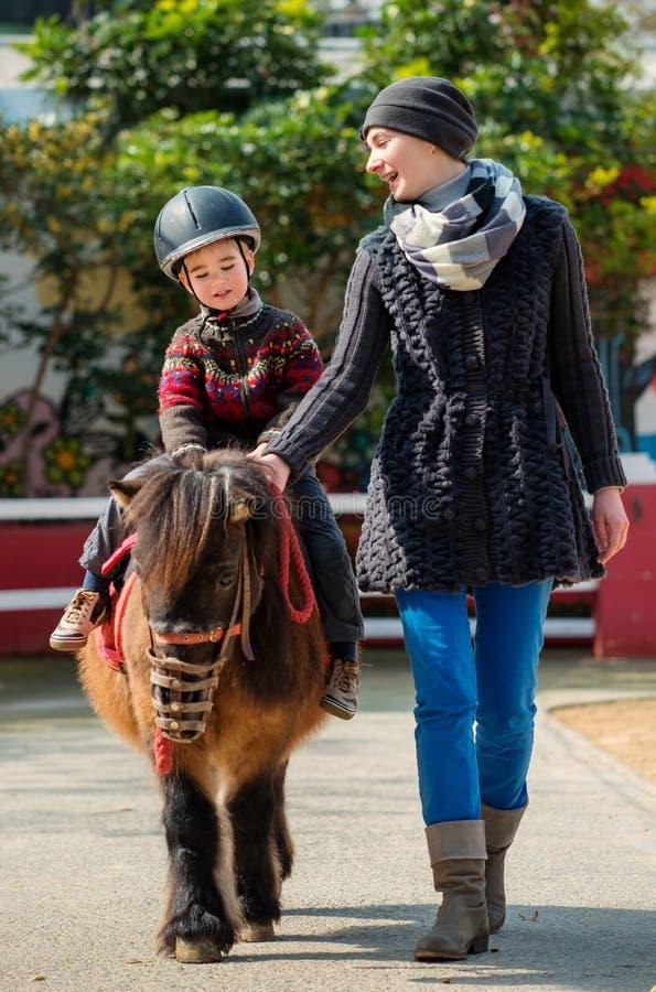 Équitation d'enfant sur un poney photos stock