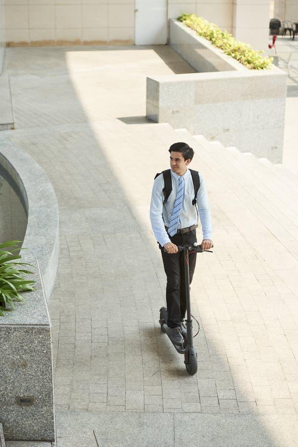Équitation d'homme sur le scooter à travailler photos libres de droits