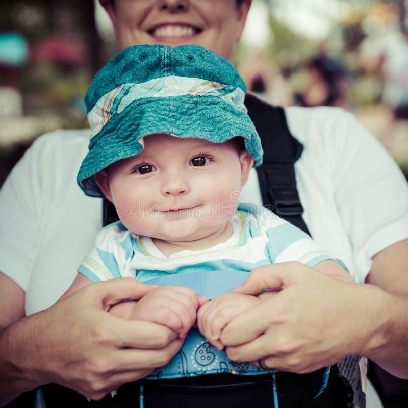 Équitation de bébé garçon dans le transporteur infantile par la mère photographie stock