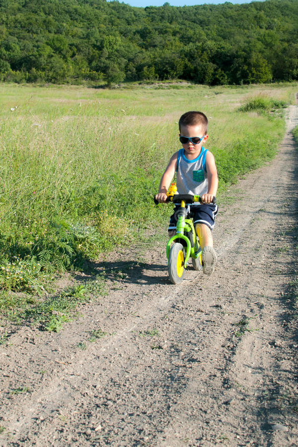 Équitation de bébé garçon sur son premier vélo sans pédales images libres de droits