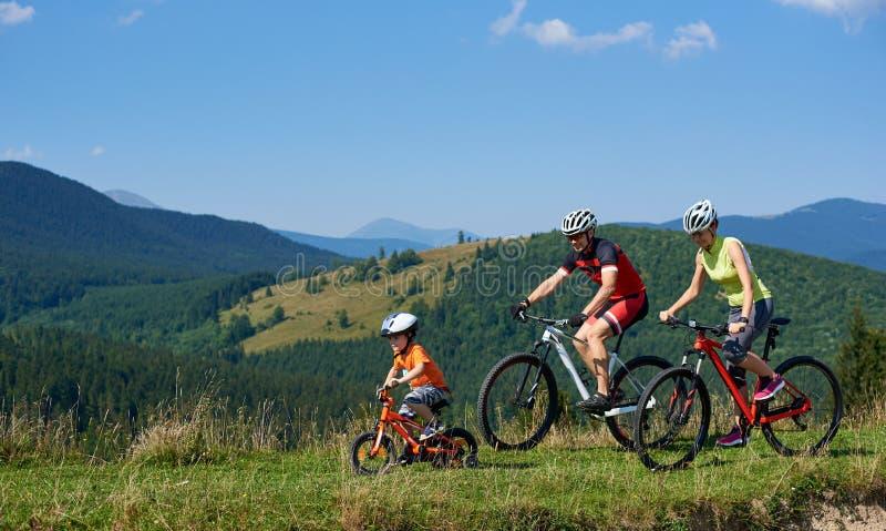 Équitation de cyclistes, de maman, de papa et d'enfant de touristes de famille sur des bicyclettes sur la colline herbeuse photo libre de droits