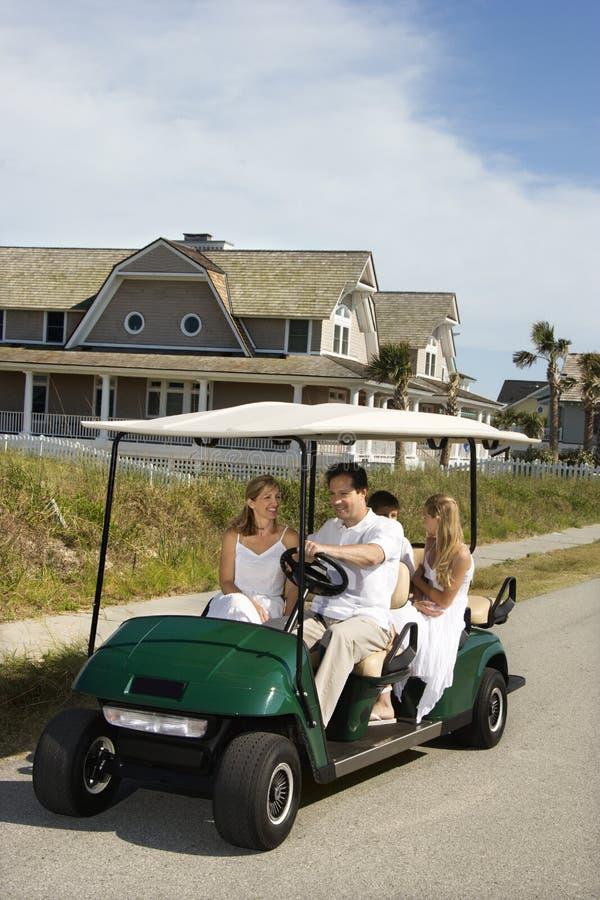 Équitation de famille dans le chariot de golf. photos libres de droits