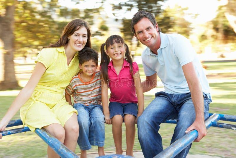Équitation de famille sur le rond point en stationnement photographie stock