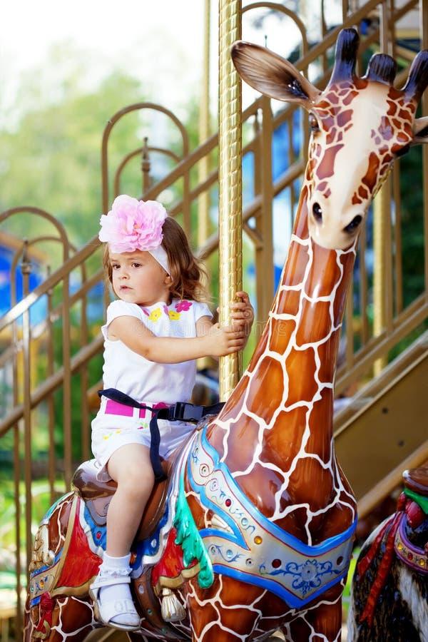 Équitation de fille sur un carrousel images stock