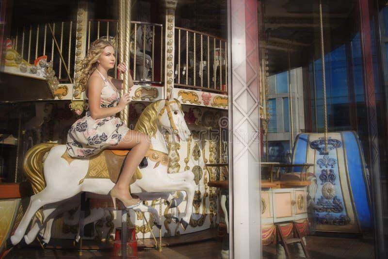 Équitation de fille sur un cheval blanc sur un carrousel photo stock