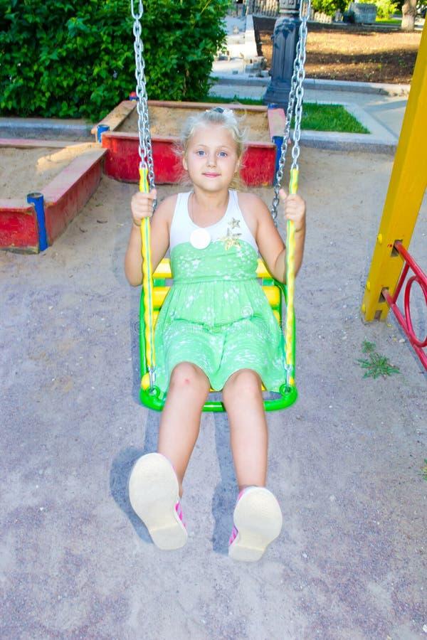 Équitation de fille sur une oscillation photos stock