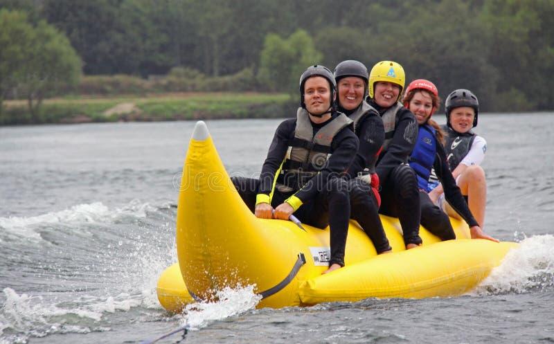 Équitation de gens sur un bateau de banane photos libres de droits