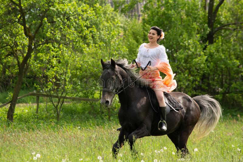 Équitation de jeune femme sur le beau cheval, ayant l'amusement dans l'heure d'été, campagne de la Roumanie photographie stock