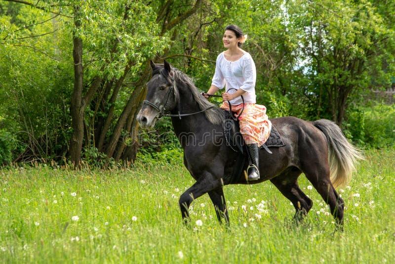 Équitation de jeune femme sur le beau cheval, ayant l'amusement dans l'heure d'été, campagne de la Roumanie photos stock