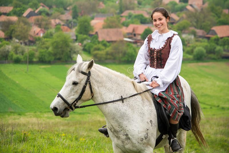 Équitation de jeune femme sur le beau cheval, ayant l'amusement dans l'heure d'été, campagne de la Roumanie photographie stock libre de droits