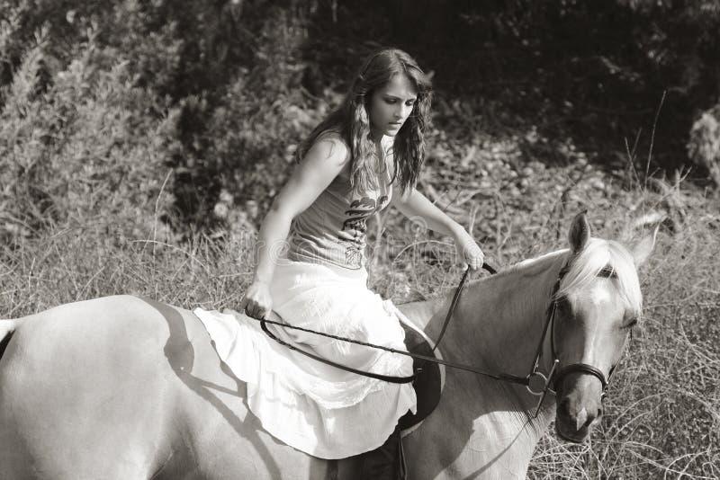 Équitation de jeune femme sur le cheval (tache floue de mouvement) image stock