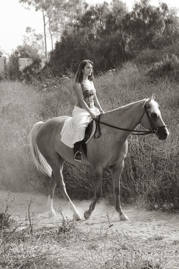 Équitation de jeune femme sur le cheval (tache floue de mouvement) images stock