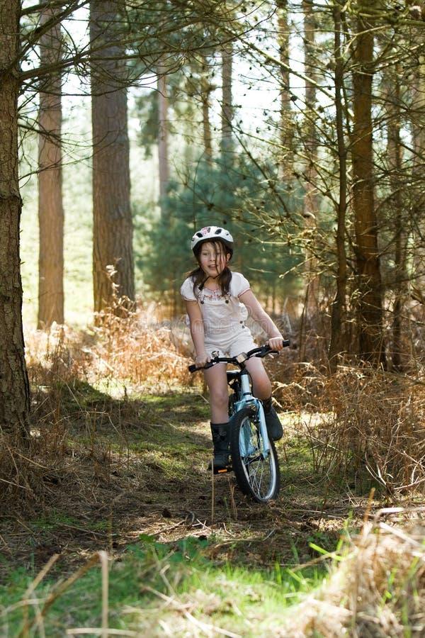 Équitation de jeune fille son vélo dans la forêt images stock