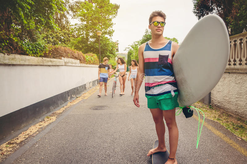 Équitation de jeune homme sur le patin et la planche de surf de participation photo stock