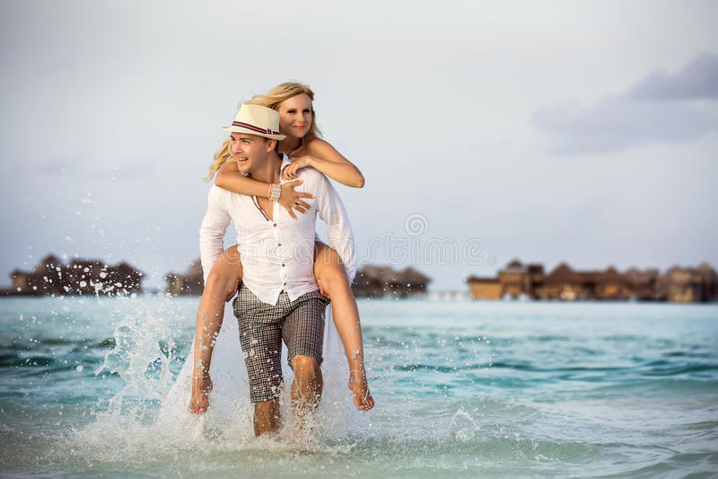 Équitation de jeune mariée sur le marié image stock