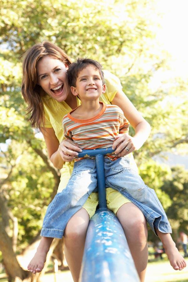 Équitation de mère et de fils sur la balançoir dans la cour de jeu images libres de droits