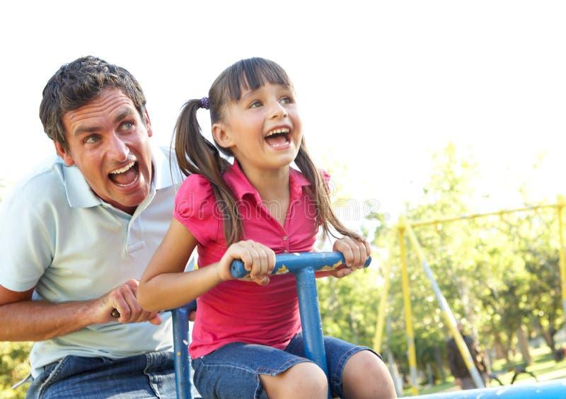Équitation de père et de descendant sur la balançoir dans la cour de jeu photo libre de droits