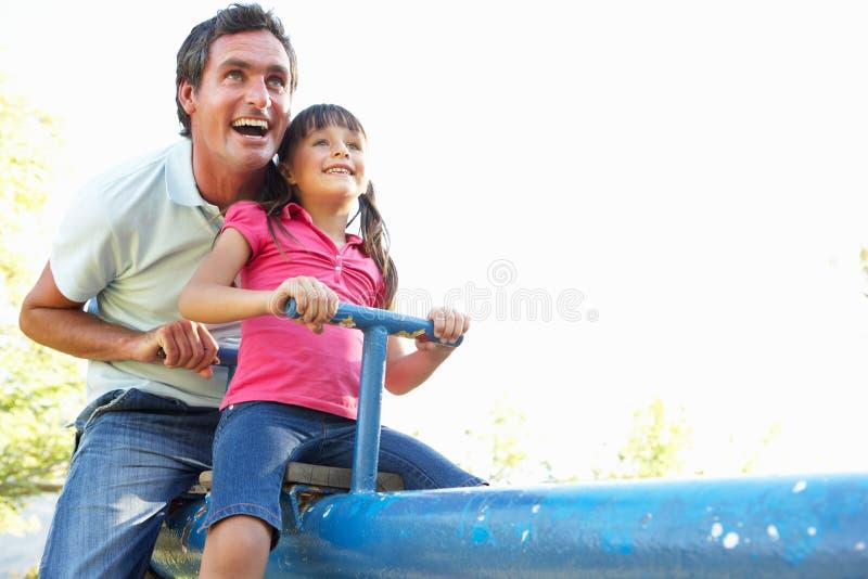 Équitation de père et de descendant sur la balançoir dans Playgroun images stock