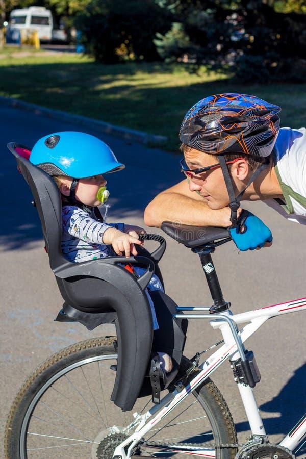 Équitation de père et de fils à la bicyclette avec la chaise de vélo photographie stock libre de droits