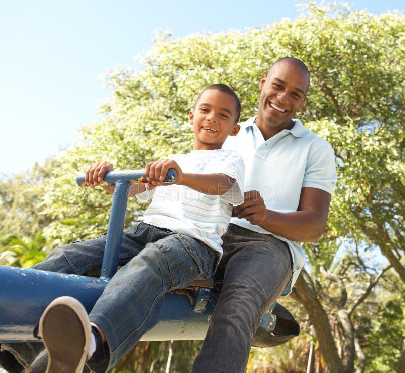 Équitation de père et de fils sur la balançoir en stationnement photos libres de droits
