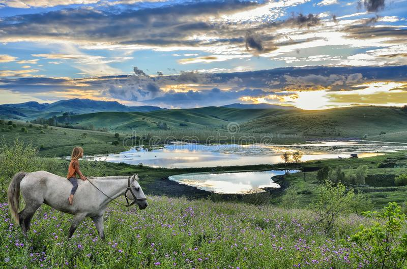 Équitation de petite fille sur le cheval blanc en montagne au coucher du soleil image stock