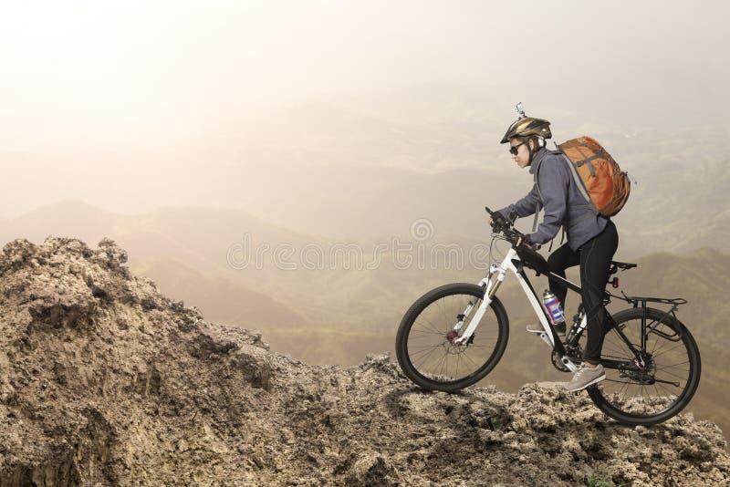 Équitation femelle de cycliste sur la bicyclette en montagnes image libre de droits