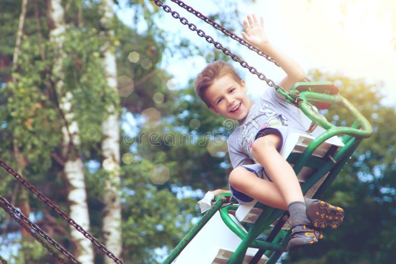 Équitation heureuse de garçon en parc image stock