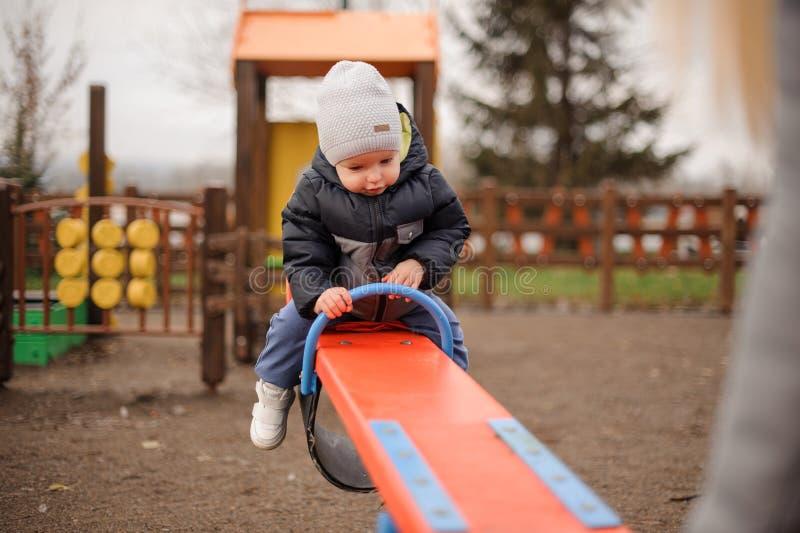 Équitation mignonne de petit garçon sur l'oscillation et regard vers le bas photographie stock