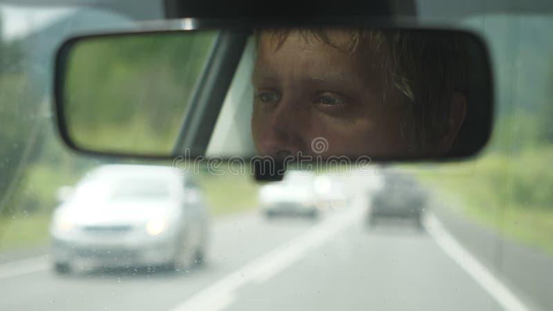 Équitation réfléchie d'homme dans la voiture par des montagnes pendant le jour pluvieux photos libres de droits