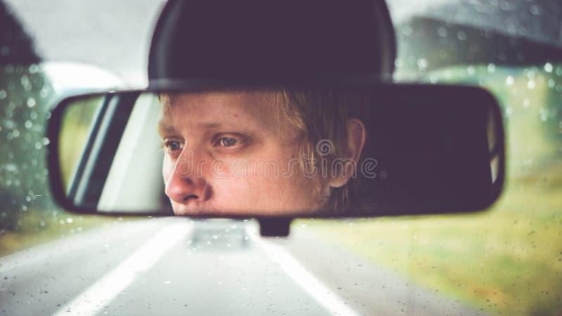 Équitation réfléchie de jeune homme dans la voiture par des montagnes pendant le jour pluvieux photo stock