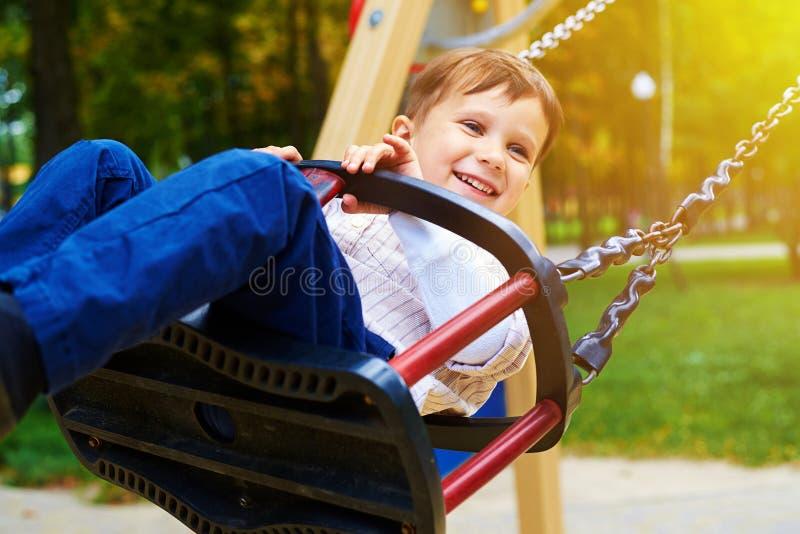 Équitation souriante de petit garçon sur une oscillation image stock