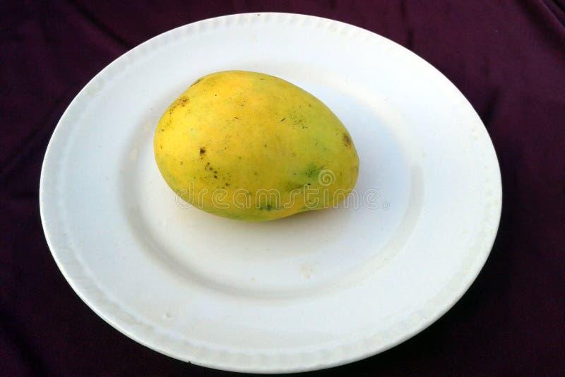 Ésta es la imagen de las frutas amarillas de un mango que se pone en una placa imagen de archivo libre de regalías