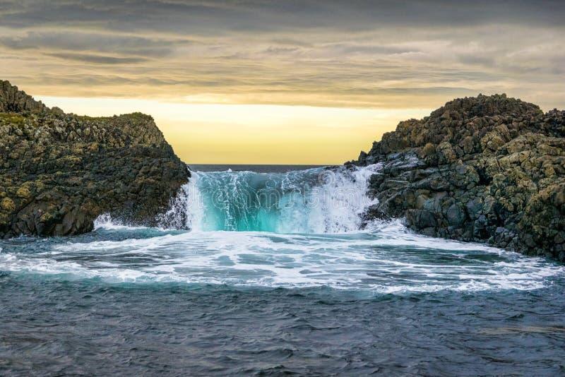 Ésta es una imagen de una onda que salpica sobre rocas en el mar en la puesta del sol foto de archivo libre de regalías