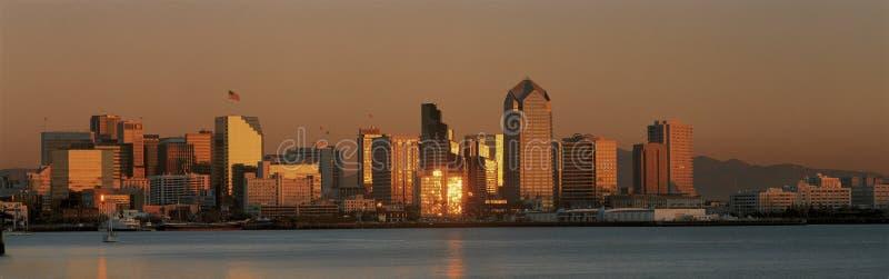 Éste es el horizonte de San Diego con la bahía en frente en la puesta del sol La luz reflejada en los edificios es de oro imagenes de archivo