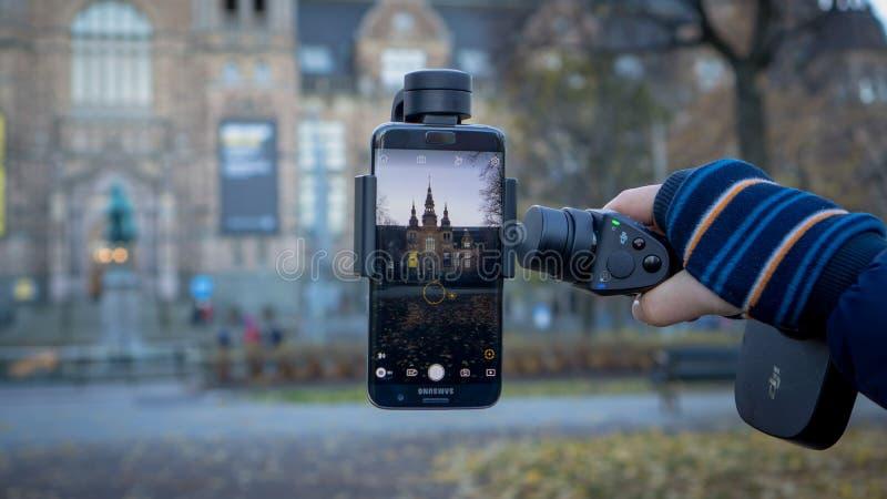 Éstocolmo, Suécia - 28 de outubro de 2016: Dispositivo da suspensão Cardan de DJI Osmo Mobile com o telefone de Android Samsung imagem de stock royalty free
