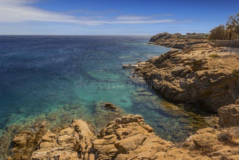 Été : Île de Mykonos, Grèce Beau paysage de côte rocheuse : les eaux azurées de la mer Égée, de la falaise, des roches et des pie photos stock