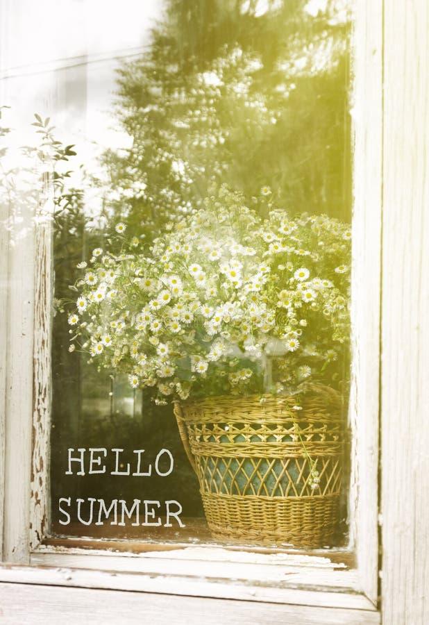 Été d'inscription bonjour sur le fond d'un bouquet avec des marguerites dans un panier sur la fenêtre rustique photo libre de droits