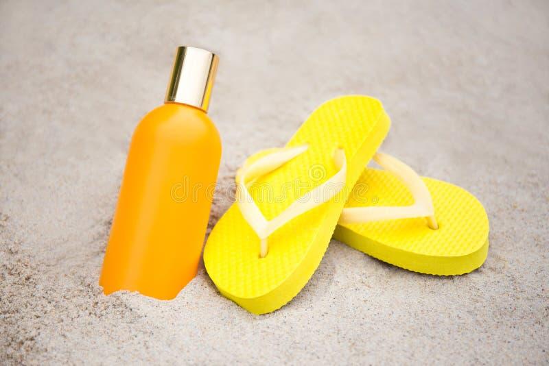 Été et concept de soins de la peau - pantoufles et bouteille de lotion de bronzage photos stock