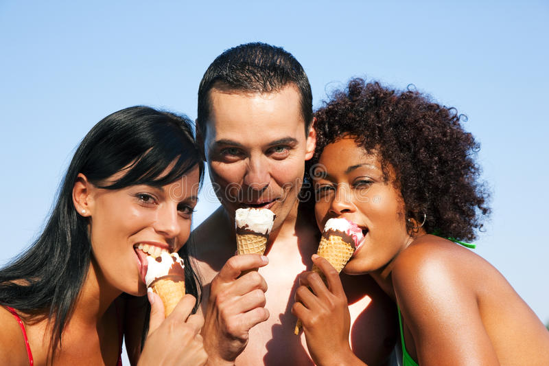 Été - homme et deux femmes mangeant la glace sur la plage photos libres de droits
