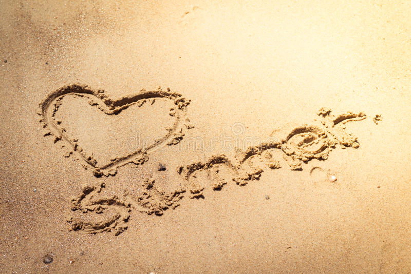 Été manuscrit dans le sable de la plage avec un beau coeur photos libres de droits