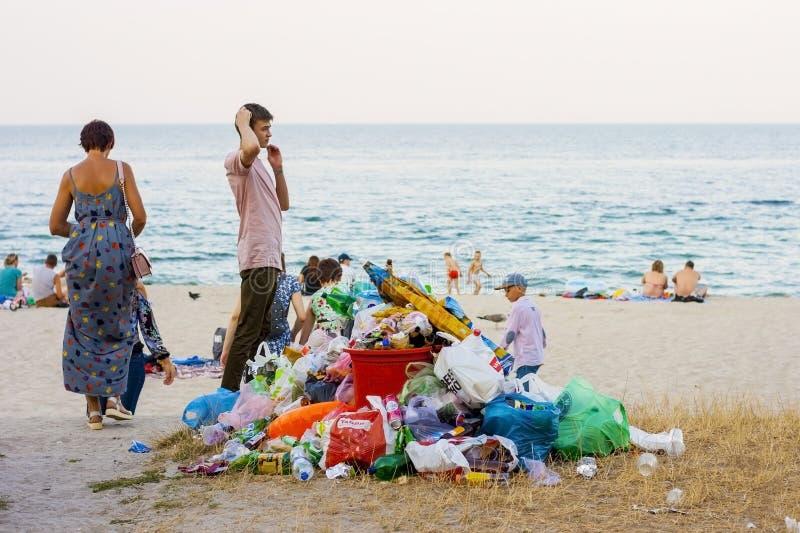Été 2019, pile d'Odessa, Ukraine A des déchets sur la plage urbaine de sable à côté des personnes détendant sur la mer L'économie photographie stock