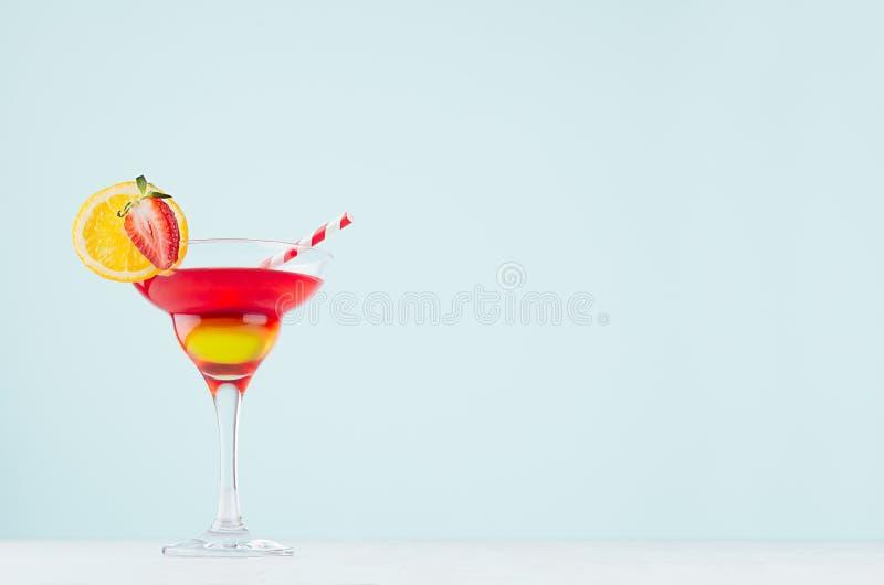 Été régénérant la boisson posée avec la boisson alcoolisée rouge et jaune, la tranche orange et la paille dans le verre à vin sur images stock