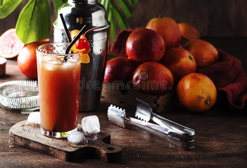 Été régénérant le bas cocktail alcoolique avec la vodka, le jus d'orange, l'orange ensanglantée et les glaçons Table en bois Foye images stock