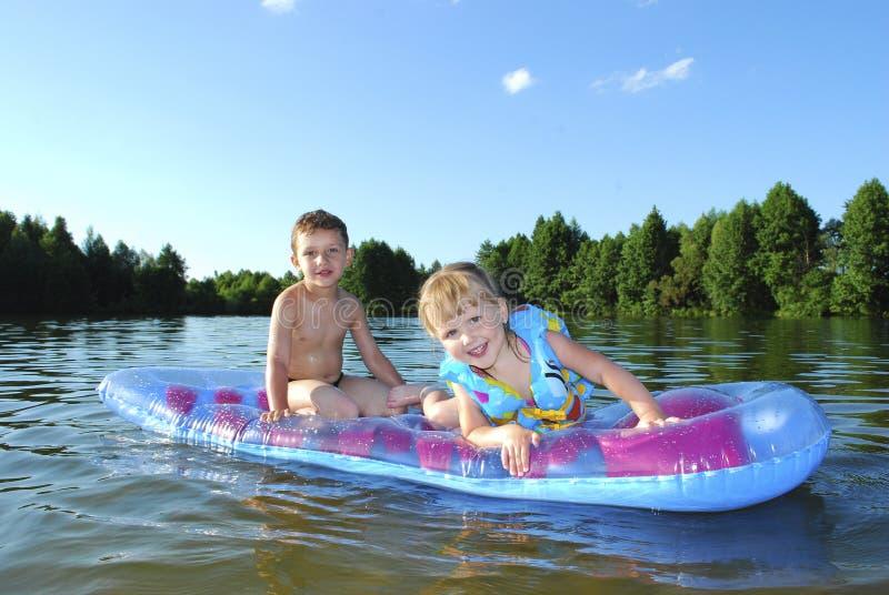 Été sur le garçon et la fille de rivière flottant sur un matelas d'air. image libre de droits