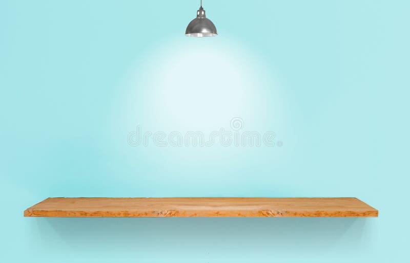 Étagère en bois avec la lampe sur le mur bleu de vintage images stock