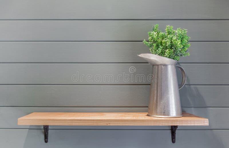 Étagère en bois sur le mur de planche avec le vase de la fleur en plastique images libres de droits