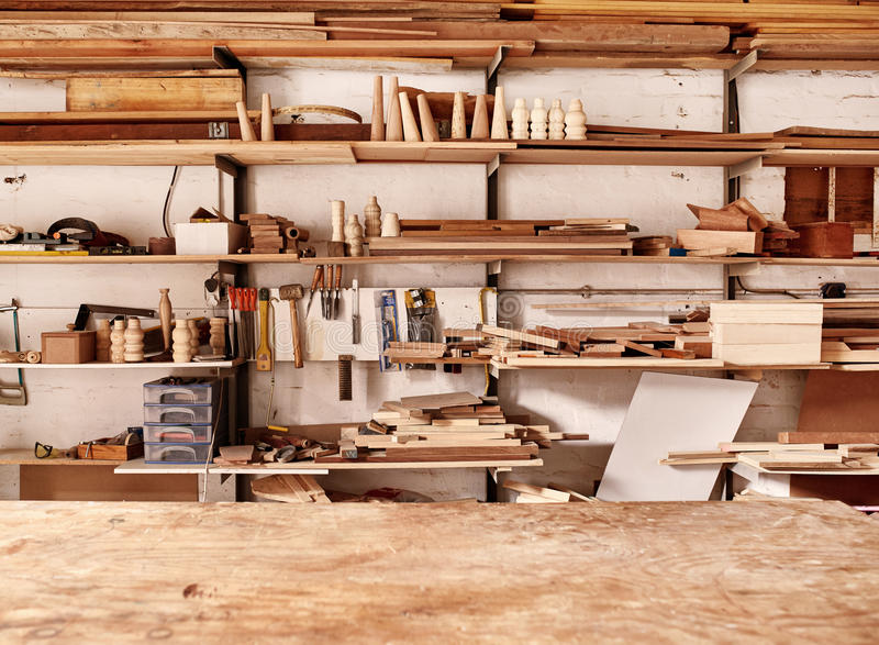 Étagères dans l'atelier de boisage avec de divers articles et outils en bois images stock