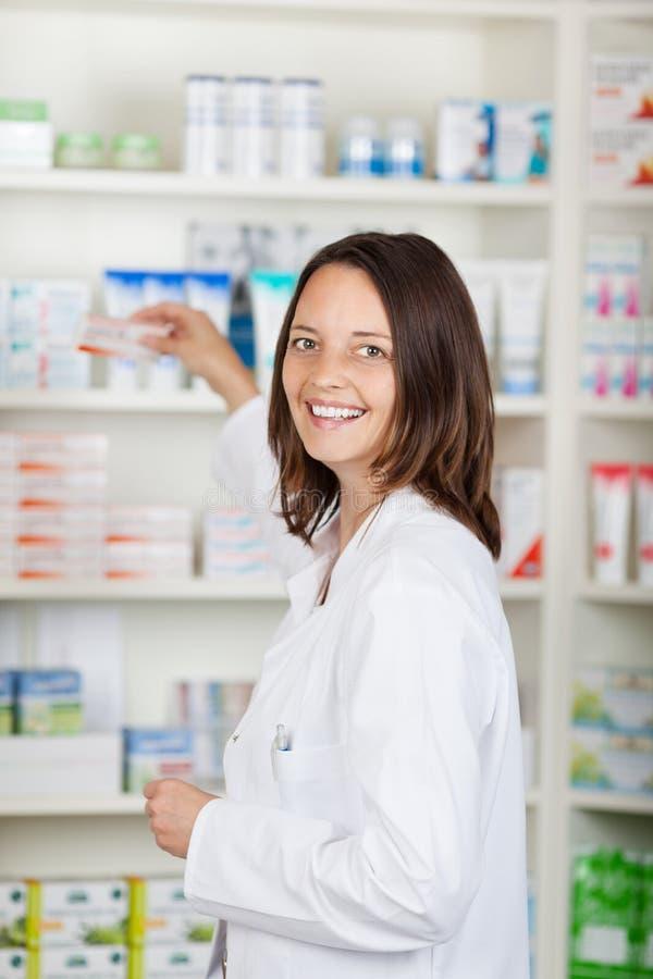 Étagères de Taking Medicine From de pharmacien à la pharmacie photo libre de droits