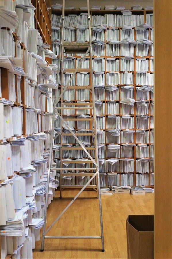 Étagères en bois grandes avec des papiers, partout dans les murs entièrement, un dépôt de document, une échelle de recherche sur  image stock