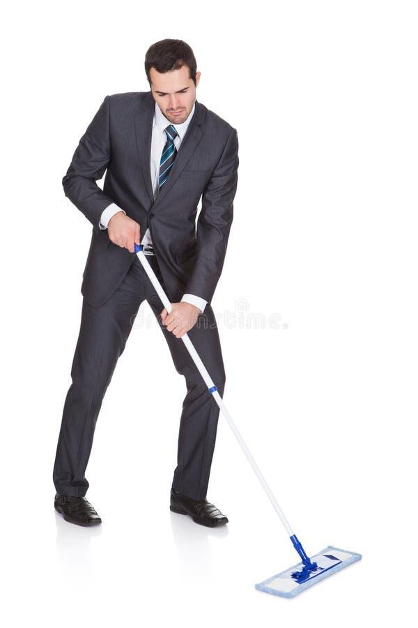 Étage de nettoyage d'homme d'affaires image stock